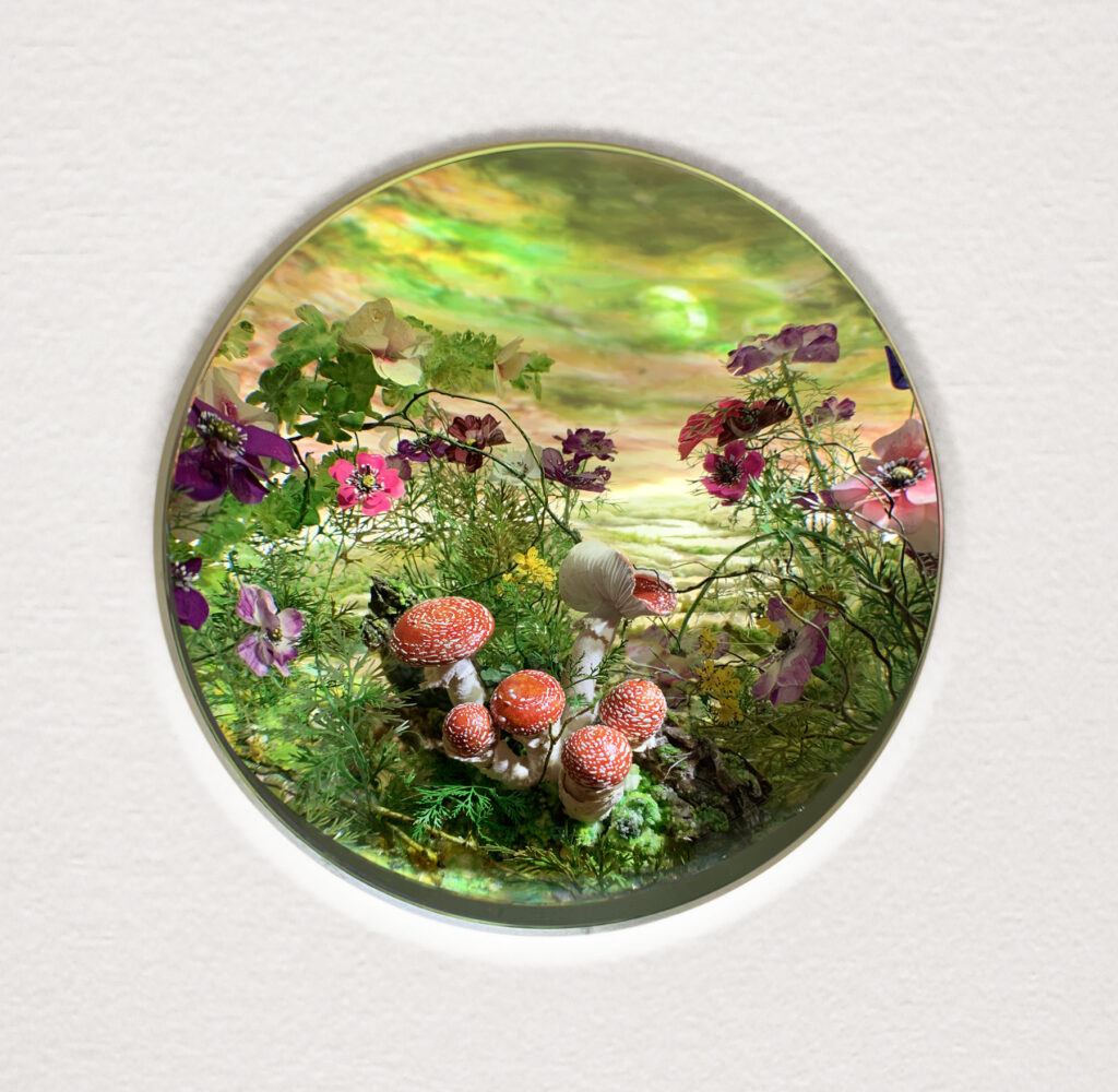 """Patrick Jacobs, Fly Agarics with Eclipse, 2021, diorama viewed through 2 in. (5 cm) window, Styrene, clay, paper, foam, wood, acrylic, steel, lighting, BK7 glass, 11 1/4"""" (H) x 14 3/4"""" (W) x 9 1/4"""" (D)"""